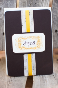invitation front on espresso stock with birch bark band, golden yellow satin ribbon and double mounted monogram plate with corner rounding